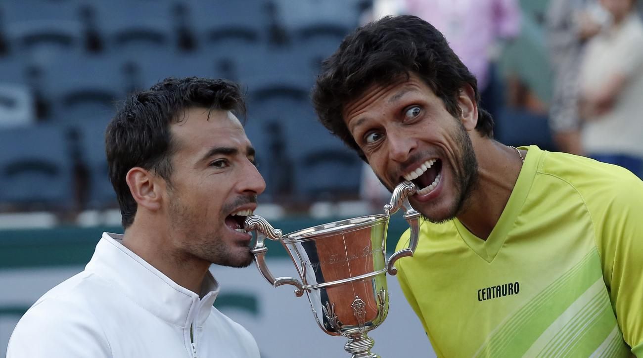 Croatia's Ivan Dodig, left, and Brazil's Marcelo Melo bite the cup after defeating Bob and Mike Bryan of the U.S. in their men's doubles final match of the French Open tennis tournament at the Roland Garros stadium, Saturday, June 6, 2015 in Paris. Dido a