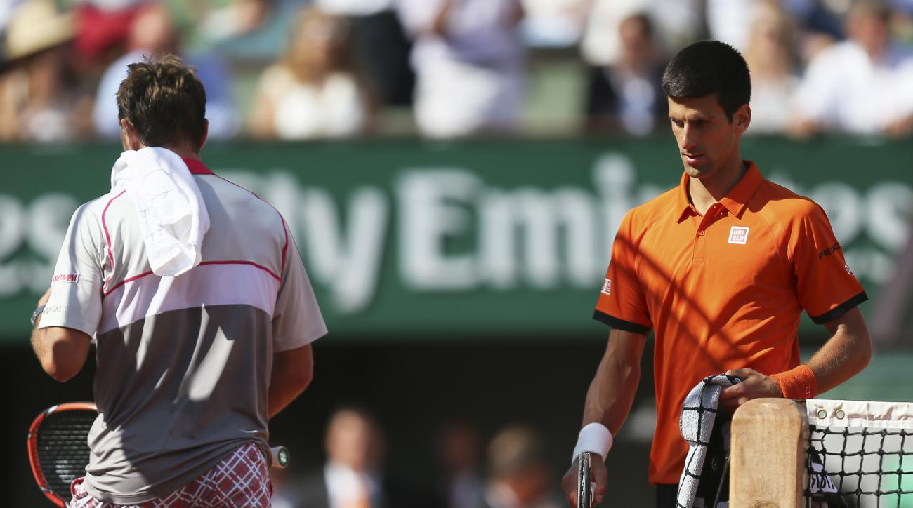 Serbia's Novak Djokovic, right, passes Switzerland's Stan Wawrinka in the men's final of the French Open tennis tournament at the Roland Garros stadium, in Paris, France, Sunday, June 7, 2015. (AP Photo/David Vincent)