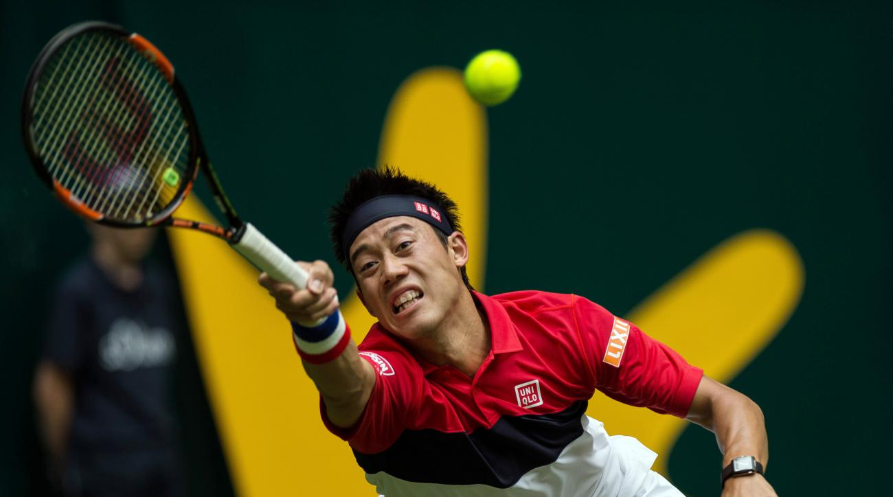 Kei Nishikori of Japan returns the ball to Austria's Dominic Thiem during their first round match at the Gerry Weber Open tennis tournament in Halle, Germany, Tuesday, June 16, 2015. (Maja Hitij/dpa via AP)