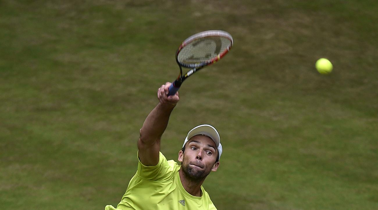 Ivo Karlovic of Croatia serves the ball to Tomas Berdych of Czech Republic during their quarterfinal match at the Gerry Weber Open ATP tennis tournament in Halle, Germany, Friday, June 19, 2015. (AP Photo/Martin Meissner)