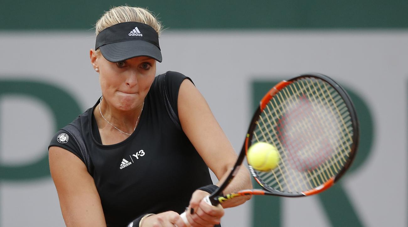 France's Kristina Mladenovic returns the ball to Canada's Eugenie Bouchard during their first round match of the French Open tennis tournament at the Roland Garros stadium, Tuesday, May 26, 2015 in Paris. Mladenovic won 6-4, 6-4. (AP Photo/Francois Mori)