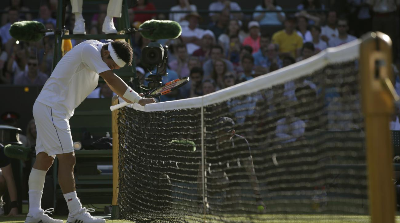 Kei Nishikori of Japan waits to greet Simone Bolelli of Italy at the net after defeating him in the men's singles first round match at the All England Lawn Tennis Championships in Wimbledon, London, Monday June 29, 2015. (AP Photo/Pavel Golovkin)