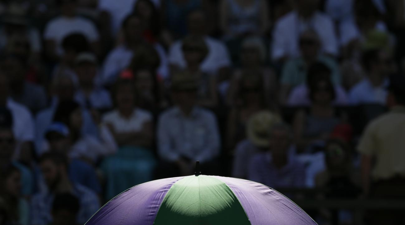 Sun rays fall on an umbrella during a break in the singles first round match between  Andy Murray of Britain and Mikhail Kukushkin of Kazakhstan at the All England Lawn Tennis Championships in Wimbledon, London, Tuesday June 30, 2015. (AP Photo/Tim Irelan