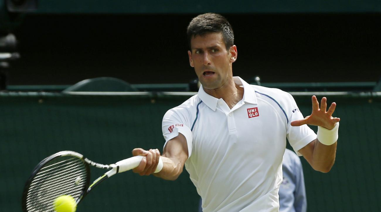 Novak Djokovic of Serbia returns to Jarkko Nieminen of Finland, during their singles match at the All England Lawn Tennis Championships in Wimbledon, London, Wednesday July 1, 2015. (AP Photo/Alastair Grant)