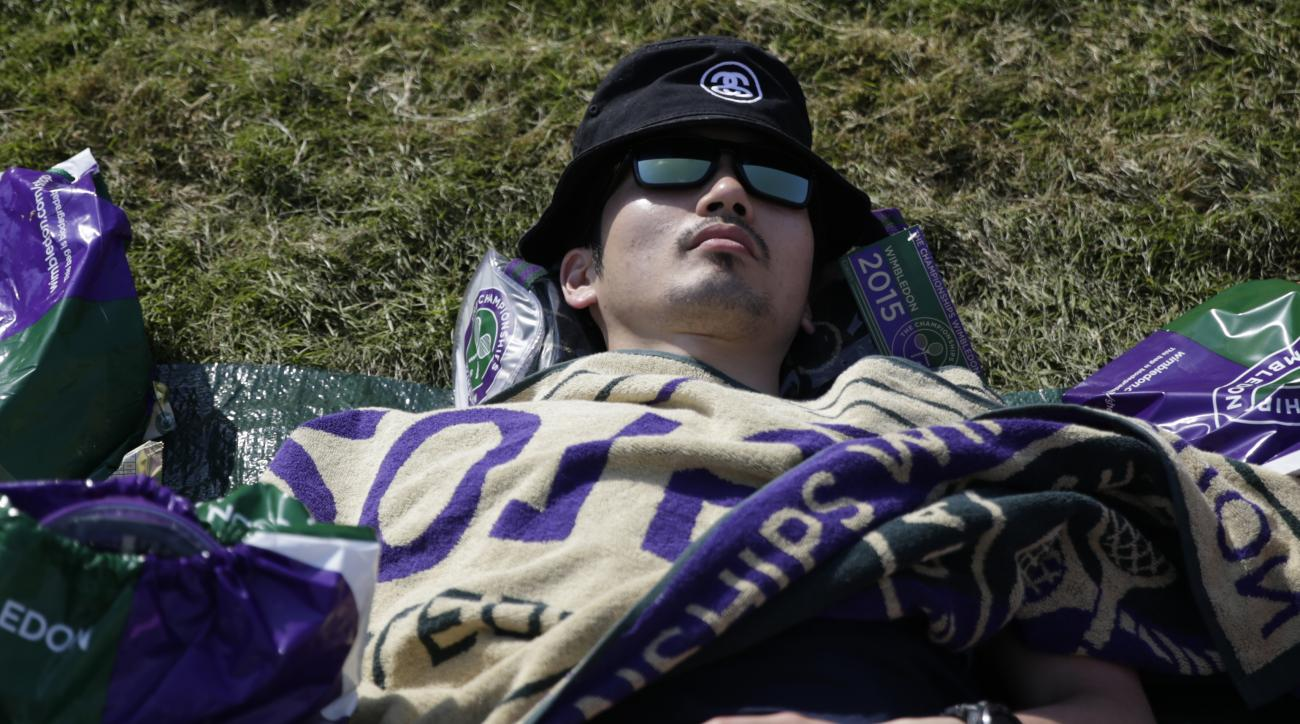 A man tries to keep cool in the heat,  on Murray Mount, at the All England Lawn Tennis Championships in Wimbledon, London, Wednesday July 1, 2015. (AP Photo/Pavel Golovkin)