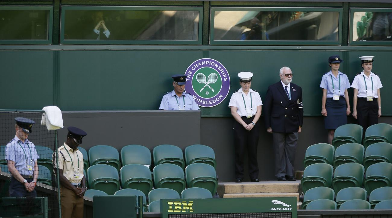 People observe the minute silence for the victims of the shooting in Tunisia last week, at the All England Lawn Tennis Championships in Wimbledon, London, Friday July 3, 2015. Fans and staff at Wimbledon observed a minute's silence for the victims of last