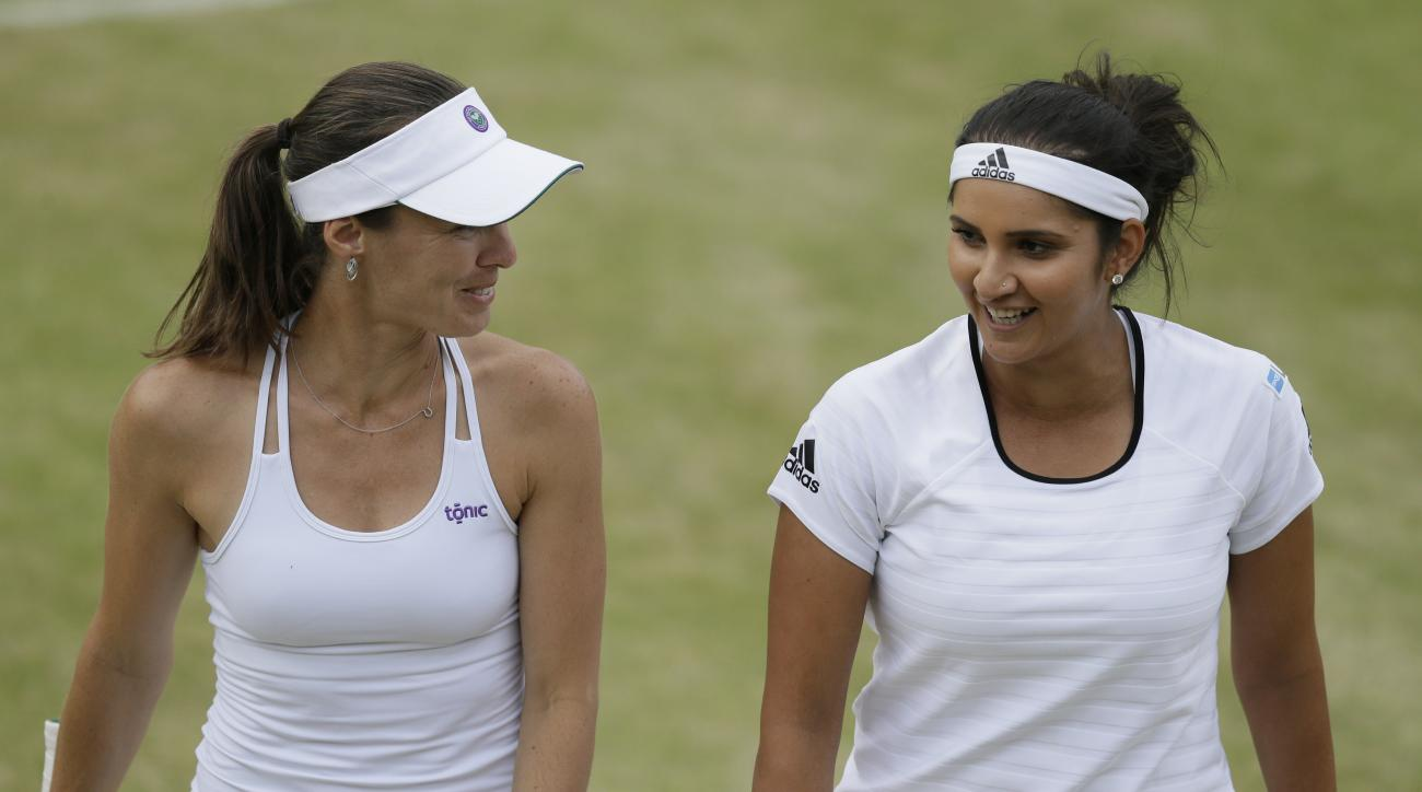 Martina Hingis from Switzerland, left, and Sania Mirza from India talk between points during their doubles match against Casey Dellacqua from Australia and Yaroslava Shvedova from Kazakhstan at the All England Lawn Tennis Championships in Wimbledon, Londo