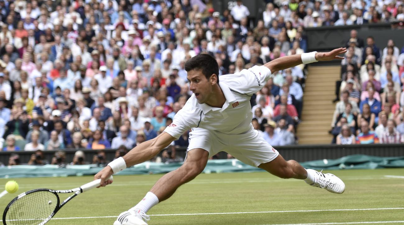 Novak Djokovic of Serbia returns a ball to Roger Federer of Switzerland during the men's singles final at the All England Lawn Tennis Championships in Wimbledon, London, Sunday July 12, 2015. (Toby Melville/Pool Photo via AP)