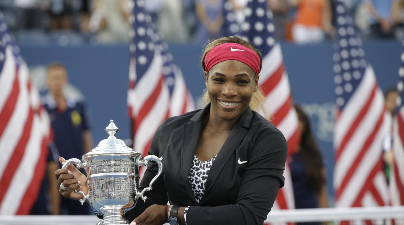 Serena Williams, of the United States, holds the championship trophy after defeating Caroline Wozniacki, of Denmark, during the championship match of the 2014 U.S. Open tennis tournament, Sunday, Sept. 7, 2014, in New York. (AP Photo/Darron Cummings)