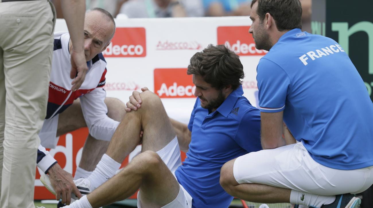 France's Gilles Simon receives treatment as he plays Britain's Andy Murray during the quarterfinal tennis matches of the Davis Cup at the Queen's Club in London, Sunday July 19, 2015. (AP Photo/Tim Ireland)