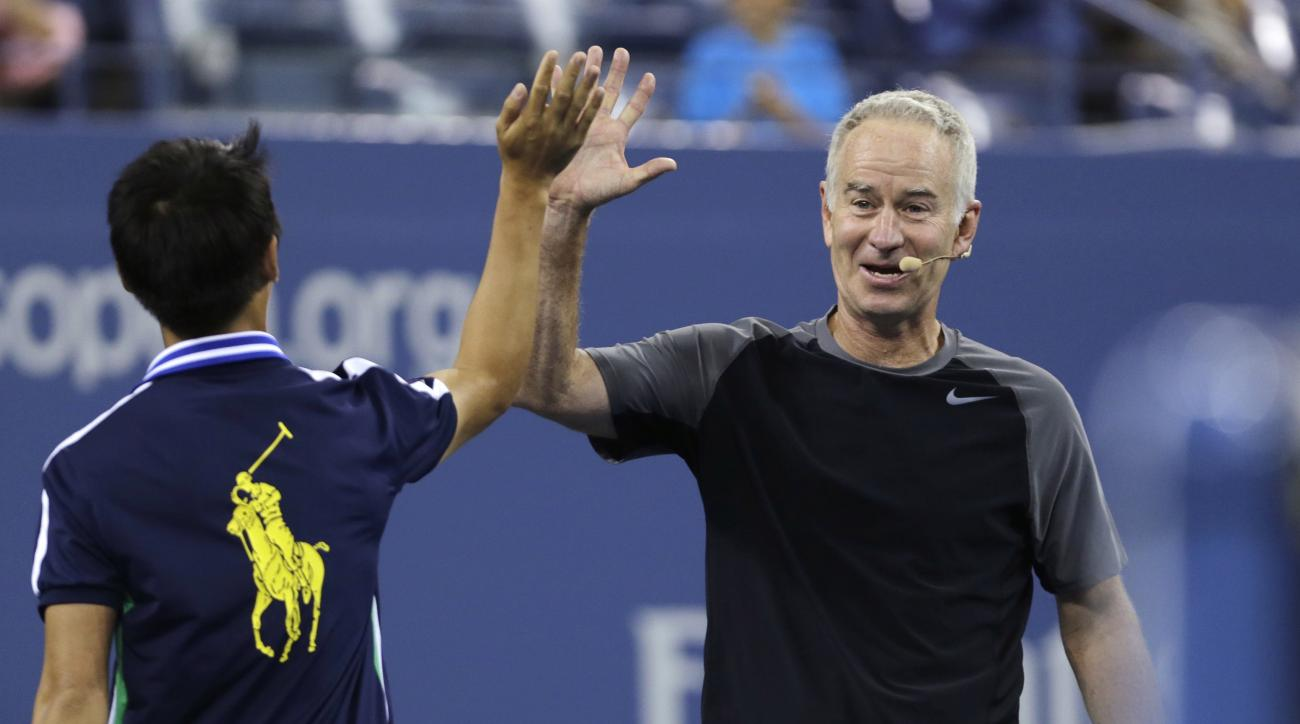 FILE - In this Sept. 4, 2014, file photo, John McEnroe high-fives a ball boy during an exhibition match prior to the quarterfinal between Roger Federer and Gael Monfils at the U.S. Open tennis tournament  in New York. John McEnroe says he's almost done pl
