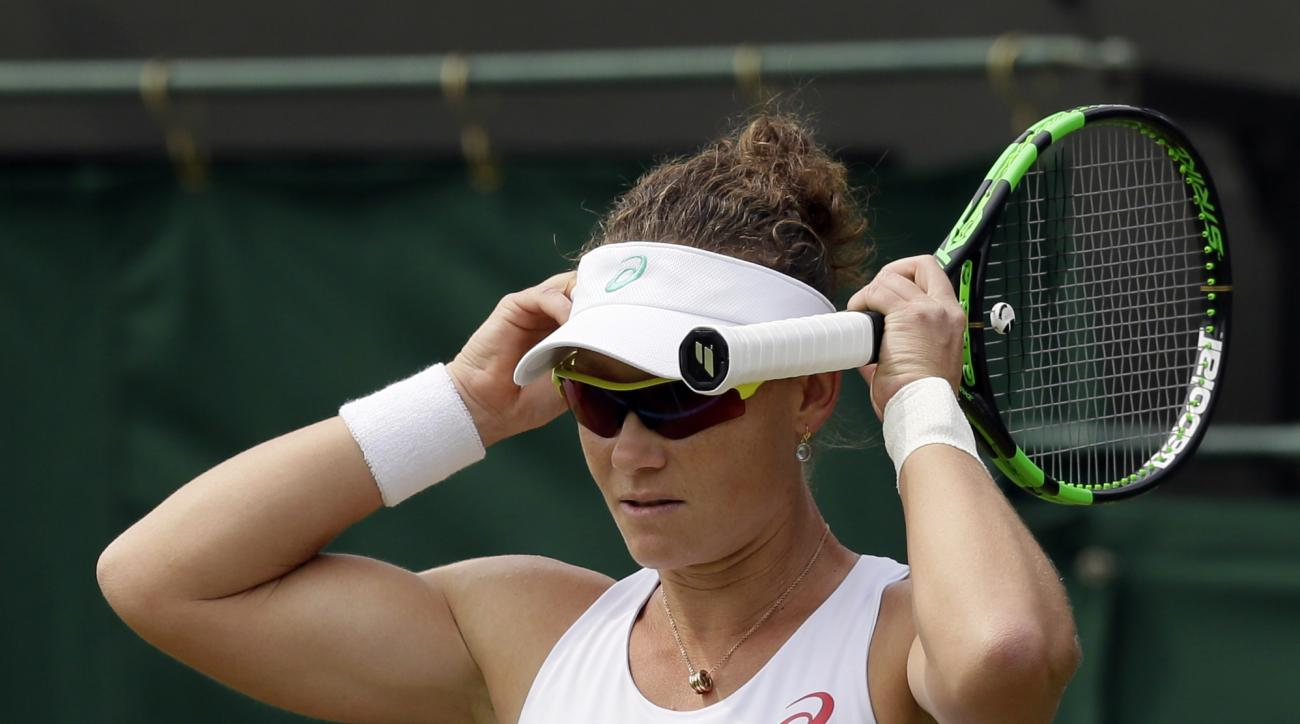 Samantha Stosur of Australia adjusts her hat as she plays Coco Vandeweghe of the United States, during their singles match at the All England Lawn Tennis Championships in Wimbledon, London, Friday July 3, 2015. (AP Photo/Tim Ireland)