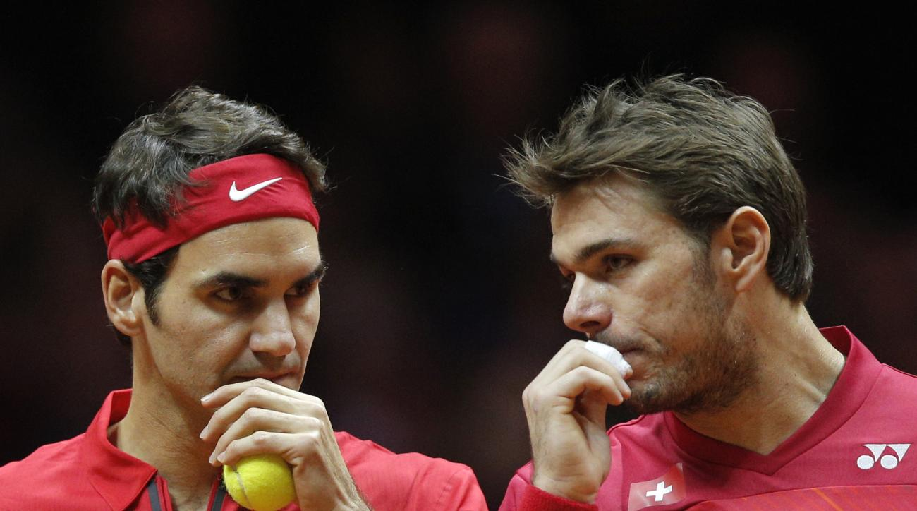 Switzerland's Roger Federer, left, and Stanislas Wawrinka chat while playing France's Julien Benneteau and Richard Gasquet during their doubles match for the Davis Cup final in Lille, northern France, Saturday, Nov.22, 2014. (AP Photo/Christophe Ena)