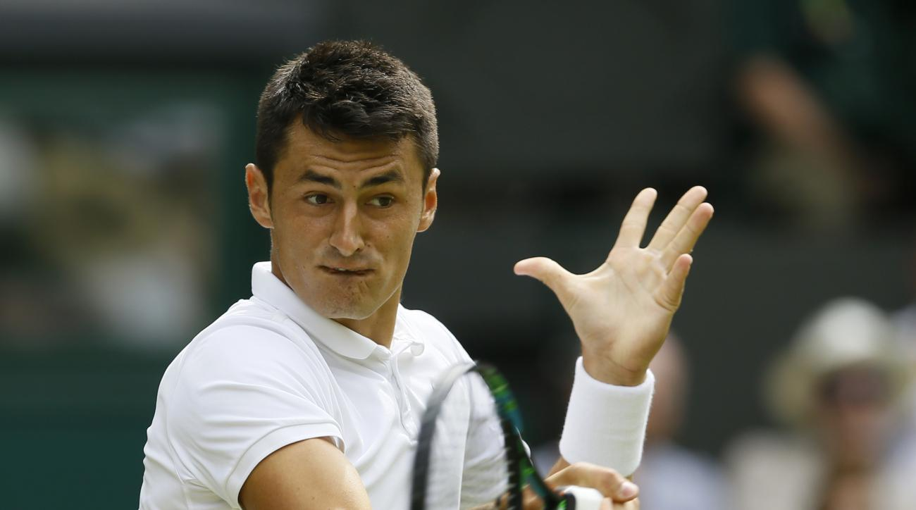 Bernard Tomic of Australia returns a ball to  Novak Djokovic of Serbia during their singles match at the All England Lawn Tennis Championships in Wimbledon, London, Friday July 3, 2015. (AP Photo/Kirsty Wigglesworth)
