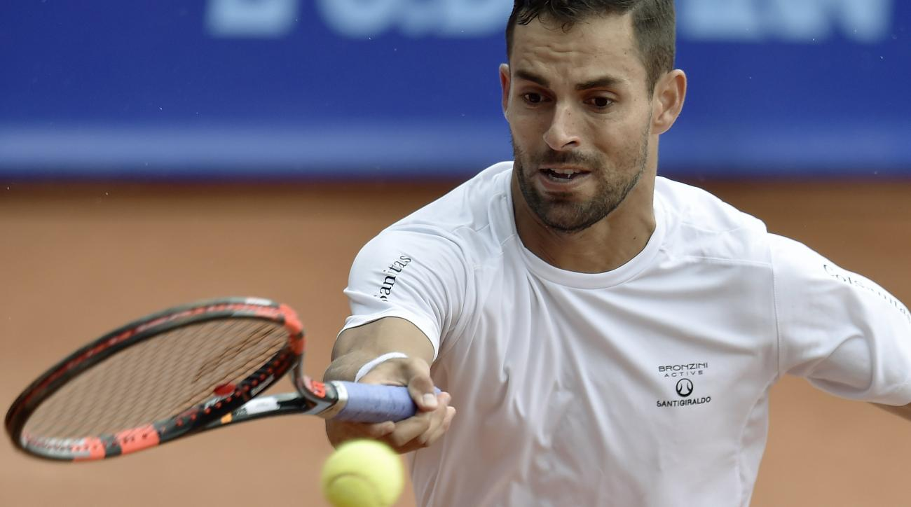 Santiago Giraldo of Columbia returns the ball to Marsel Ilhan of Turkey during their match at the Suisse Open tennis tournament in Gstaad, Switzerland, Wednesday, July 29, 2015. (Peter Schneider/Keystone via AP)