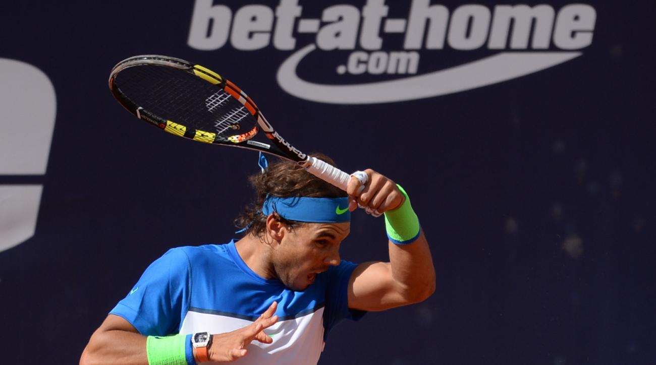 Rafael Nadal of Spain returns the ball to Pablo Cuevas of Uruguay during their quarterfinal match at the Hamburg Open tennis tournament in Hamburg, Germany, Friday, July 31, 2015. (Daniel Bockwoldt/dpa via AP)