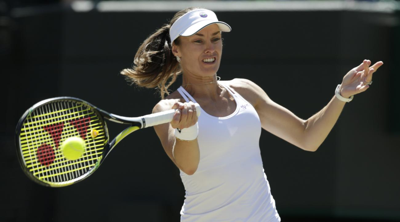 Martina Hingis of Switzerland plays a return during the women's semifinal doubles match between Raquel Kops-Jones of the United States and Abigail Spears of the United States against Hingis and Mirza of India at the All England Lawn Tennis Championships i
