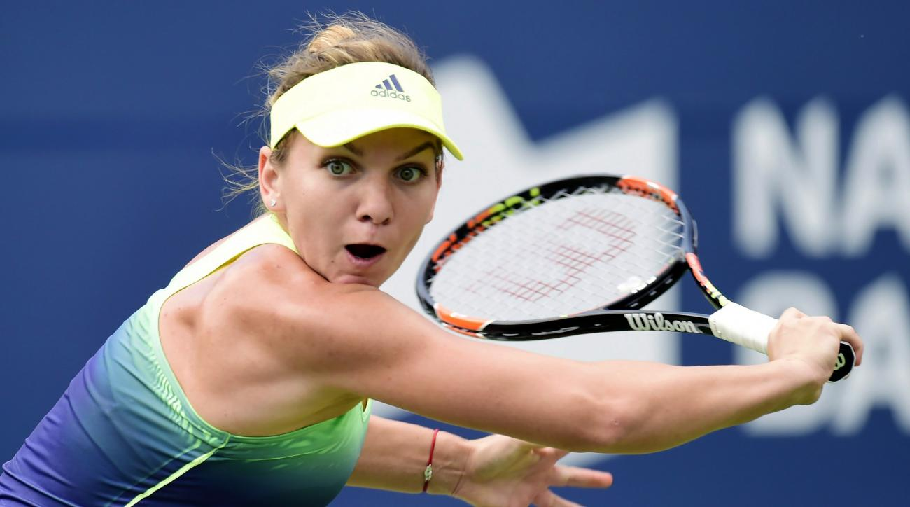 Simona Halep, of Romania, hits a return to Angelique Kerber, of Germany, during the Rogers Cup women's tennis tournament in Toronto, Thursday, Aug. 13, 2015. (Frank Gunn/The Canadian Press via AP) MANDATORY CREDIT