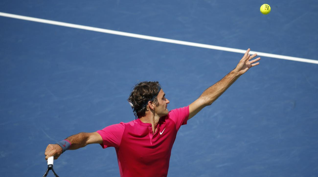 Roger Federer, of Switzerland, serves the ball to Novak Djokovic, of Serbia, during a final match at the Western & Southern Open tennis tournament, Sunday, Aug. 23, 2015, in Mason, Ohio. (AP Photo/John Minchillo)