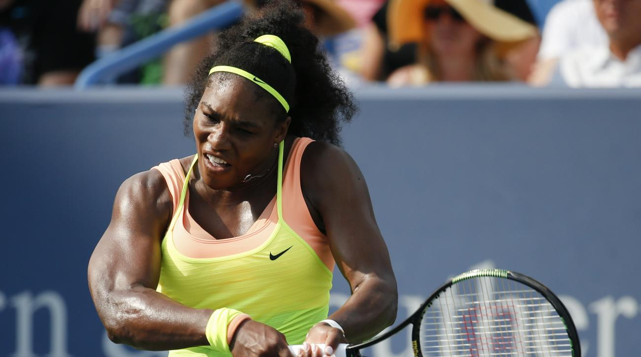 Serena Williams, of the United States, returns the ball to Simona Halep, of Romania, during the women's final at the Western & Southern Open tennis tournament, Sunday, Aug. 23, 2015, in Mason, Ohio. Williams defeated Halep 6-3, 7-6 (5). (AP Photo/John Min