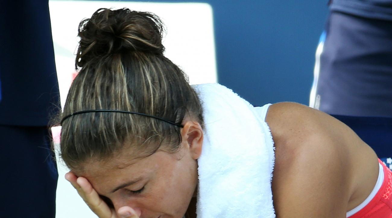 Sara Errani, of Italy, is tended to by a trainer during a break between games against Jelena Ostapenko, of Latvia, during the second round of the U.S. Open tennis tournament, Thursday, Sept. 3, 2015, in New York. (AP Photo/Adam Hunger)