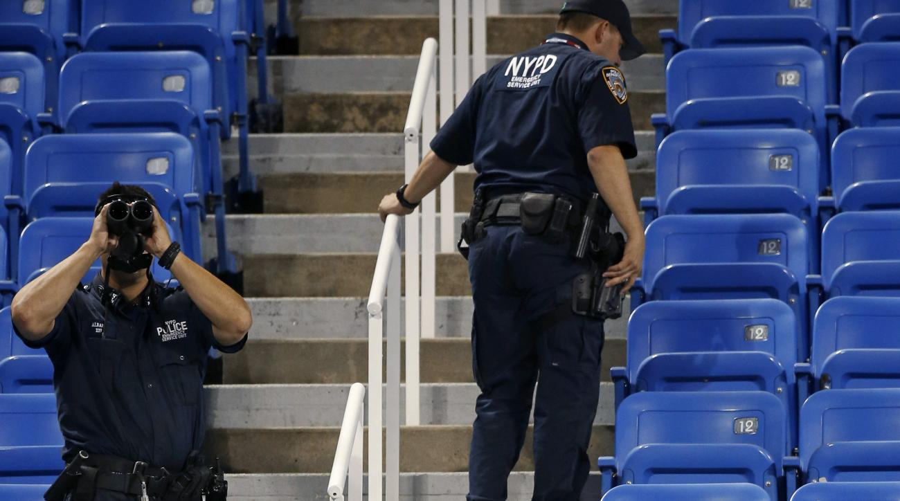 Police officers investigate the southwest corner of Louis Armstrong Stadium after a drone flew over the court, buzzing the players during a match between Flavia Pennetta, of Italy, and Monica Niculescu, of Romania, during the second round of the U.S. Open