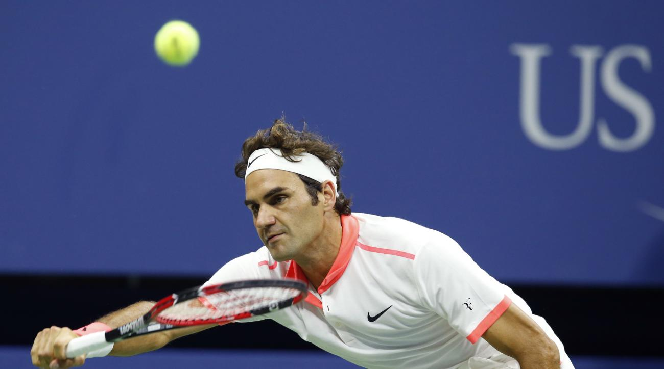 Roger Federer, of Switzerland, stretches out to return the ball during his fourth round match against John Isner at the U.S. Open tennis tournament in New York, Monday, Sept. 7, 2015.  (AP Photo/Kathy Willens)