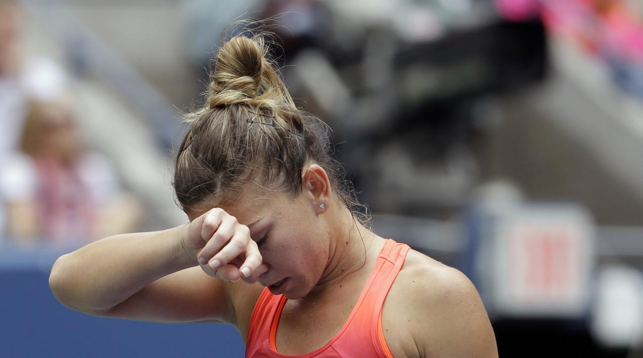 Simona Halep, of Romania, wipes sweat from her brow between points during a semifinal match against Flavia Pennetta, of Italy, at the U.S. Open tennis tournament, Friday, Sept. 11, 2015, in New York. (AP Photo/Seth Wenig)