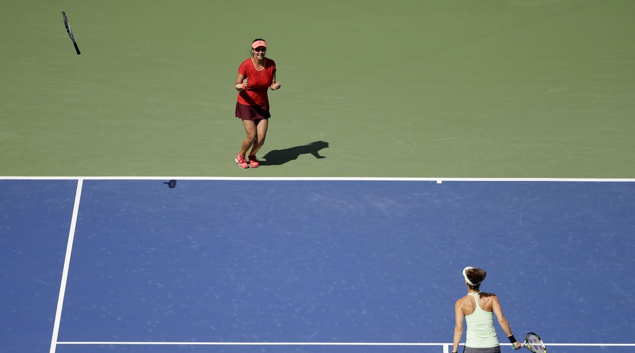 Sania Mirza, of India, left, and Martina Hingis, of Switzerland, celebrate after beating Casey Dellacqua, of Australia, and Yaroslava Shvedova, of Kazakhstan, in the women's doubles championship match of the U.S. Open tennis tournament, Sunday, Sept. 13,