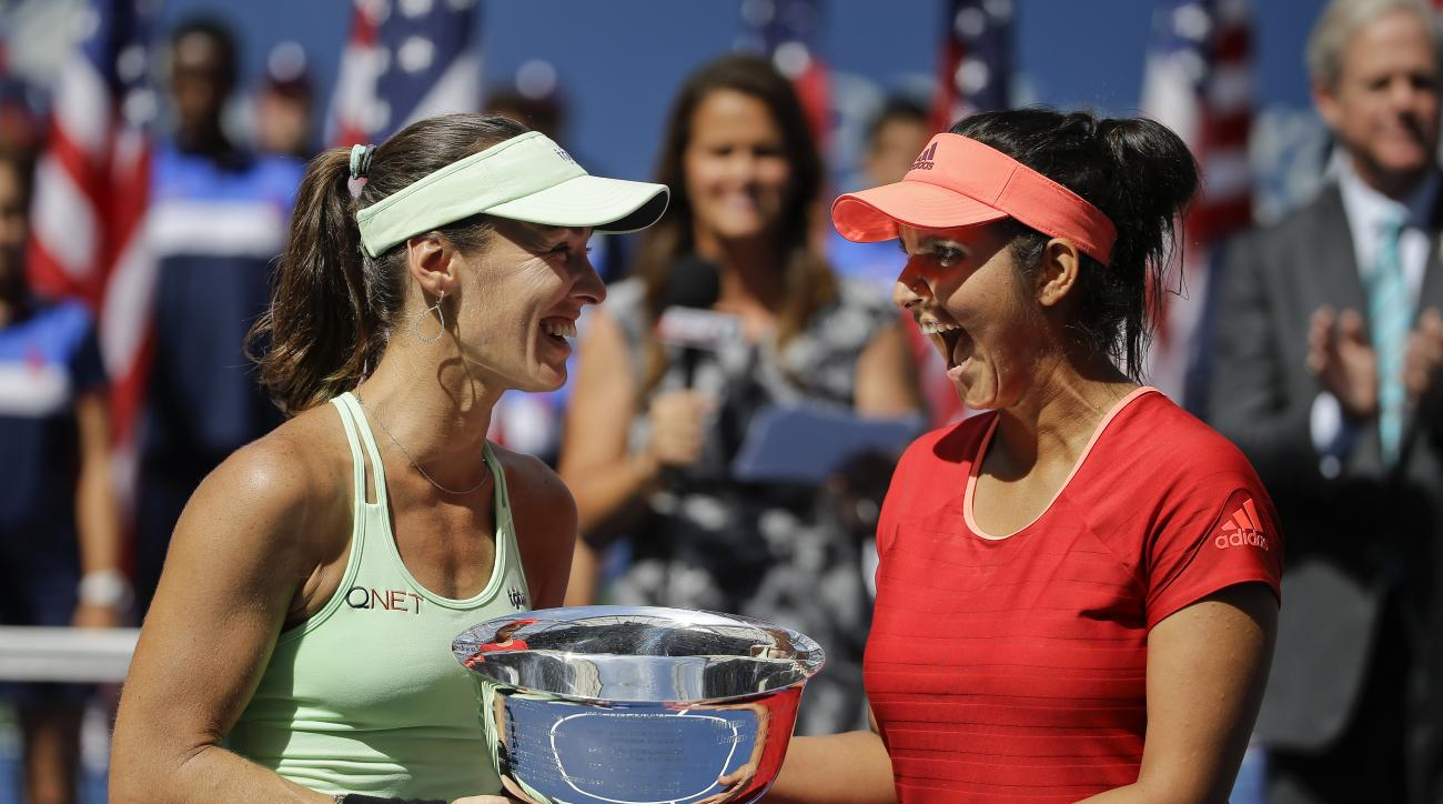 Martina Hingis, of Switzerland, left, and Sania Mirza, of India, celebrate with the championship trophy after defeating Casey Dellacqua, of Australia, and Yaroslava Shvedova, of Kazakhstan, in the women's doubles championship match of the U.S. Open tennis