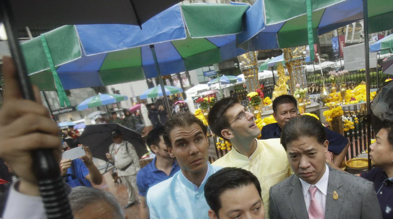 Top tennis players, Novak Djokovic of Serbia, center right, and Rafael Nadal of Spain, center left, leave after offering garlands for Phra Phrom, the Thai interpretation of the Hindu god Brahma, at the Erawan Shrine in Bangkok, Thailand, Friday, Oct. 2, 2