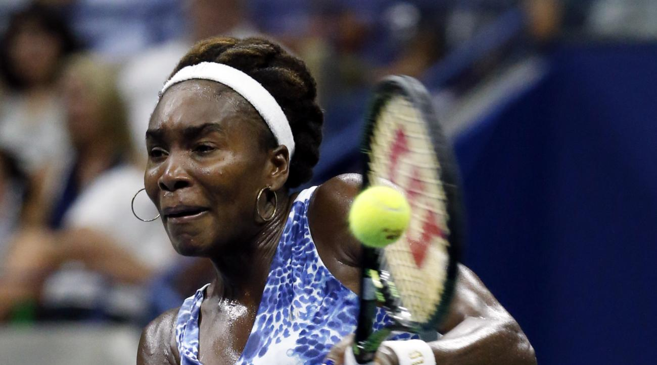 Venus Williams returns a shot to Serena Williams during a quarterfinal match at the U.S. Open tennis tournament, Tuesday, Sept. 8, 2015, in New York. (AP Photo/Julio Cortez)