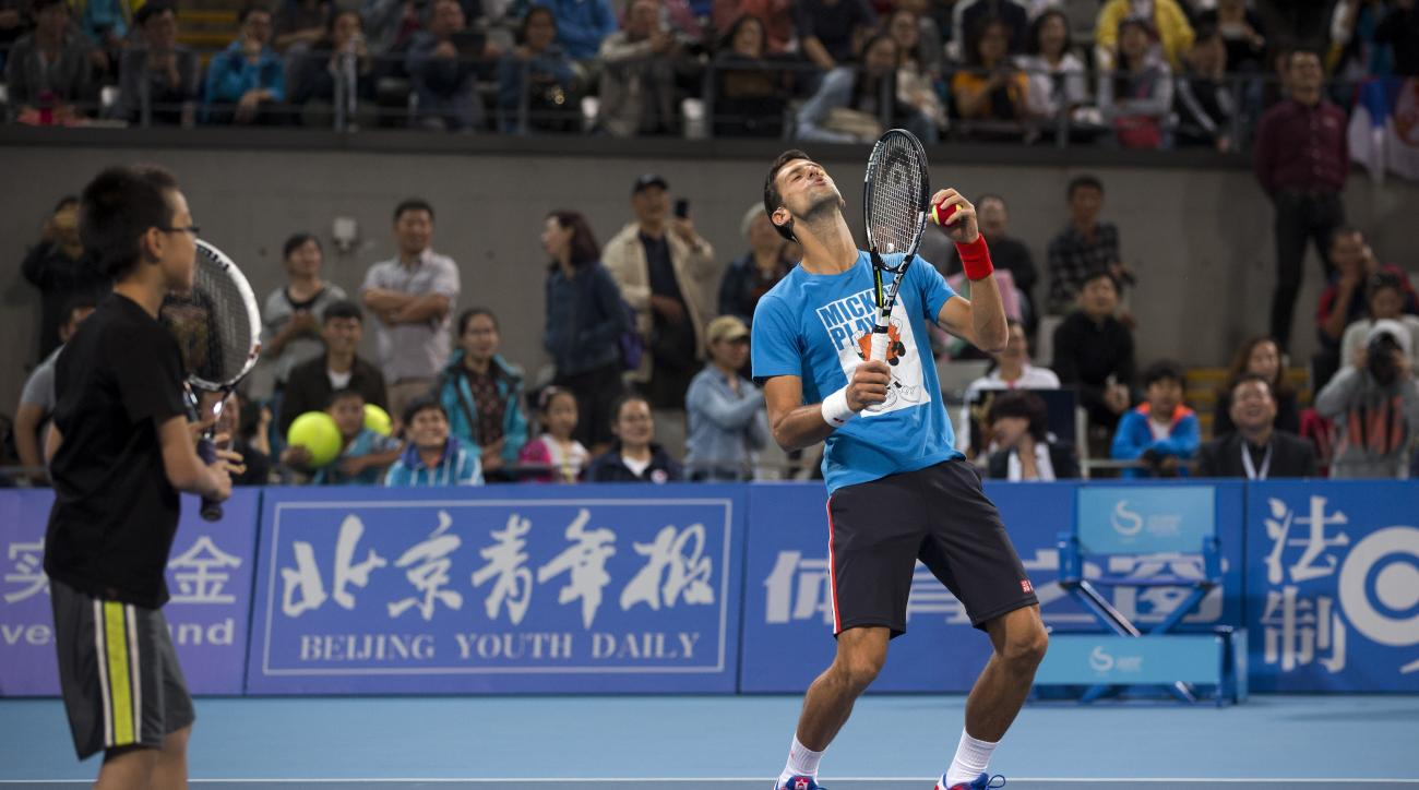 Novak Djokovic of Serbia, right, reacts as he plays with a child during a charity promotion activity event for the China Open tennis tournament at the National Tennis Stadium in Beijing, Saturday, Oct. 3, 2015 (AP Photo/Andy Wong)