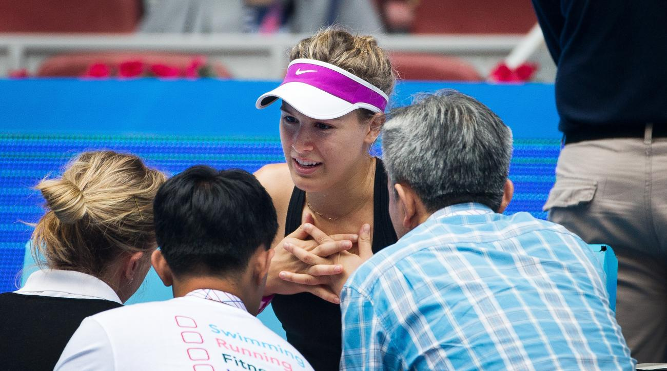 Eugenie Bouchard of Canada, center, talks with medical staff before retiring from her first round match against Andrea Petkovic of Germany at the China Open tennis tournament at the National Tennis Stadium in Beijing, Monday, Oct. 5, 2015. (AP Photo/Andy