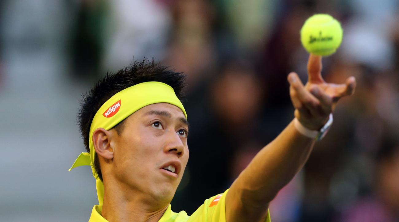 Kei Nishikori of Japan tosses a ball to serve against Sam Querrey of the United States during their singles match at the Japan Open men's tennis tournament in Tokyo, Wednesday, Oct. 7, 2015. (AP Photo/Eugene Hoshiko)