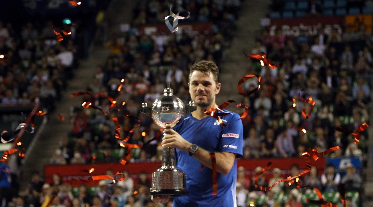 Stan Wawrinka of Switzerland  holds up the championship trophy after defeating Benoit Paire of France in the championship match of the Japan Open men's tennis tournament in Tokyo, Sunday, Oct. 11, 2015. (AP Photo/Eugene Hoshiko)