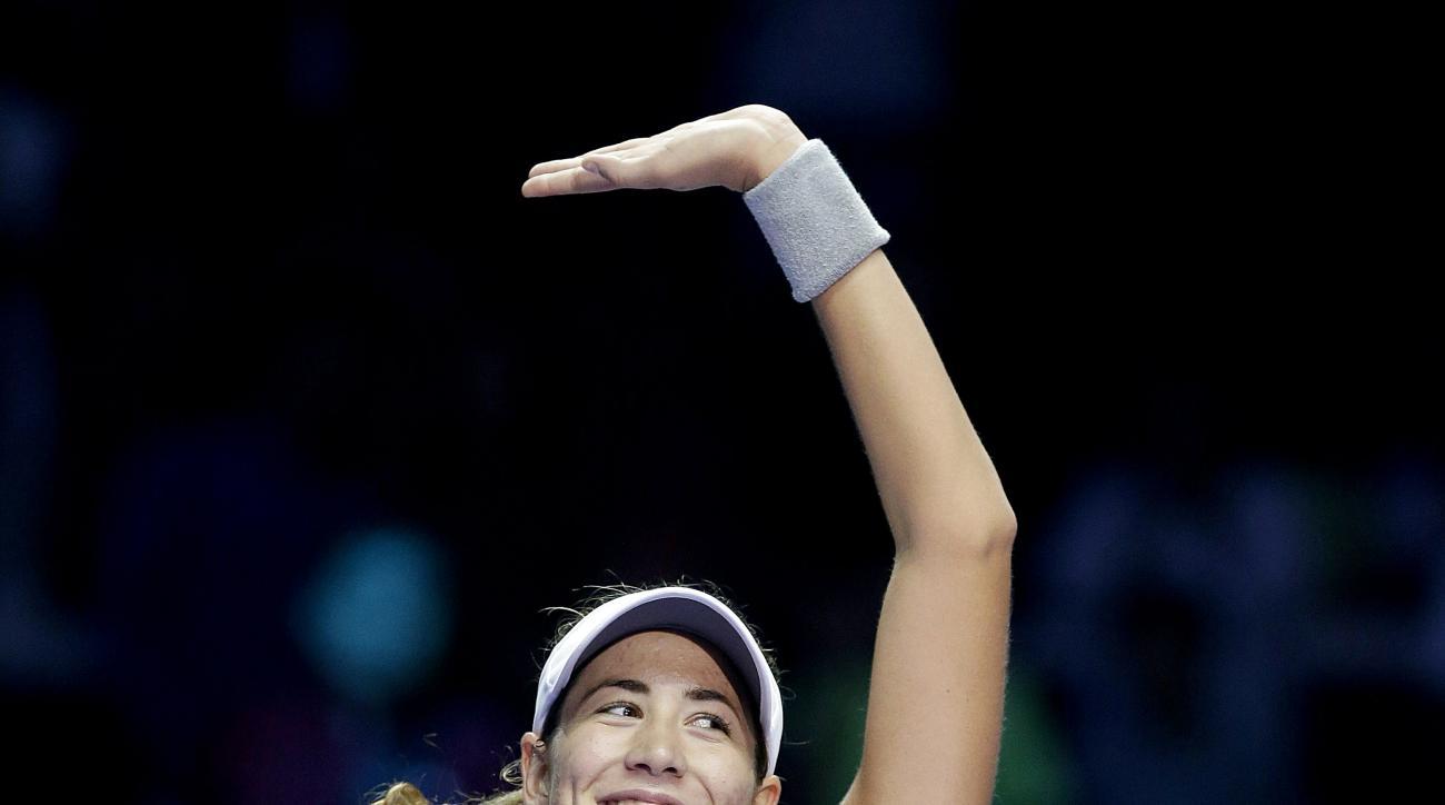 Garbine Muguruza of Spain celebrates after beating Lucie Safarova of the Czech Republic during their singles match at the WTA tennis finals in Singapore Monday, Oct. 26, 2015. (AP Photo/Wong Maye-E)