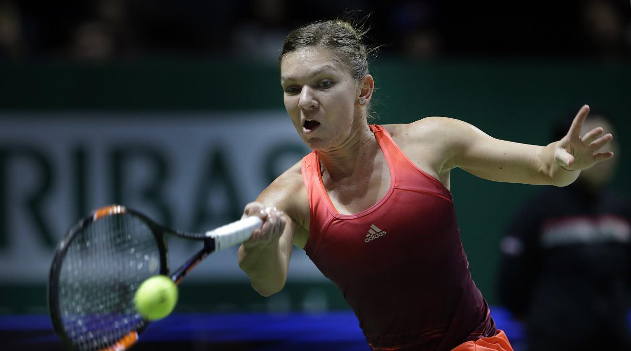 Simona Halep of Romania makes a forehand return against Agnieszka Radwanska of Poland during their singles match at the WTA tennis finals in Singapore on Thursday, Oct. 29, 2015. (AP Photo/Wong Maye-E)