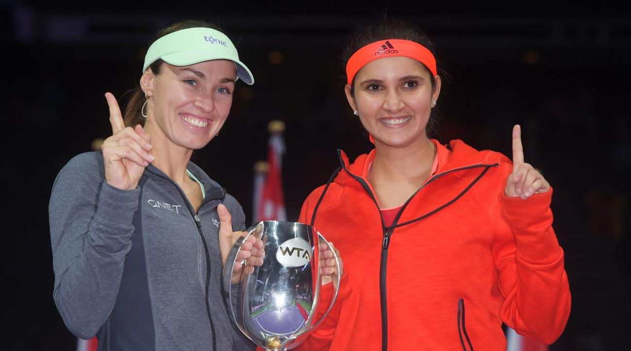 Martina Hingis of Switzerland, left, and Sania Mirza of India, right, pose with their trophy after they beat Carla Suarez Navarro and Garbine Muguruza, both of Spain during the doubles final at the WTA tennis finals in Singapore on Sunday, Nov. 1, 2015.