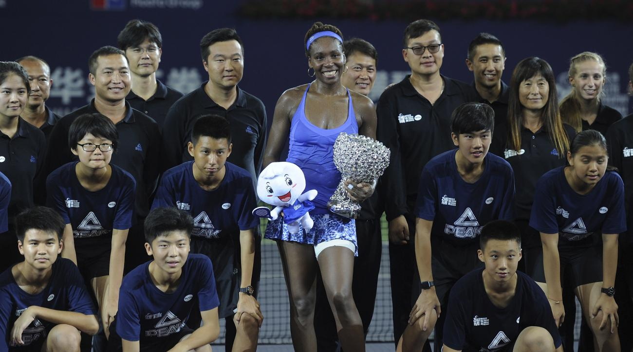Winner's Venus Williams of the United States poses with ball boys and girls after the award ceremony for the 2015 WTA Elite Trophy tennis tournament in Zhuhai in southern China's Guangdong province, Sunday, Nov. 8, 2015. Williams defeated Karolina Pliskov