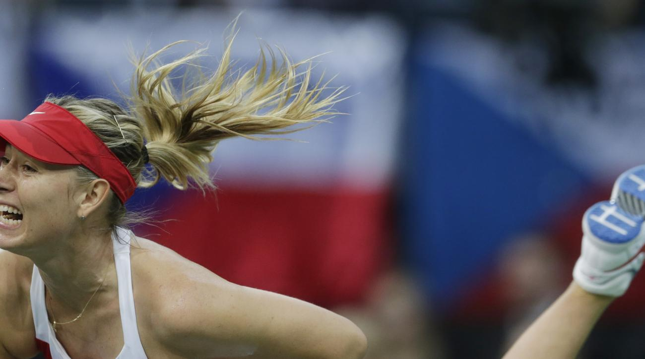 Russia's Maria Sharapova  serves  to Czech Republic's Petra Kvitova during their Fed Cup tennis final match between Czech Republic and Russia in Prague, Czech Republic, Sunday, Nov. 15, 2015. (AP Photo/Petr David Josek)