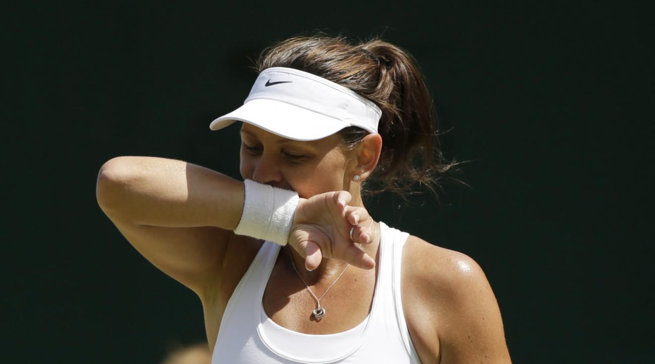 Casey Dellacqua of Australia wipes her face during the singles match against Agnieszka Radwanska of Poland at the All England Lawn Tennis Championships in Wimbledon, London, Saturday July 4, 2015. (AP Photo/Pavel Golovkin)
