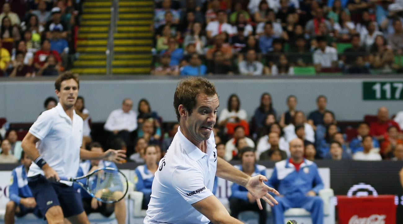 Philippine Mavericks' Richard Gasquet, foreground, hits a forehand as teammate  Edouard Roger-Vasselin both of France, looks on during the men's doubles match against the Indian Aces' Rafael Nadal of Spain and Ivan Dodig of Croatia in the 2015 Internation