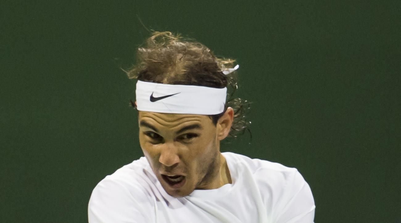 Spain's Rafael Nadal returns the ball against Illya Marchenko of Ukraine at the Qatar Open 2016 semifinals, Doha, Qatar, Friday, Jan. 8, 2016. (AP Photo/Alexandra Panagiotidou)