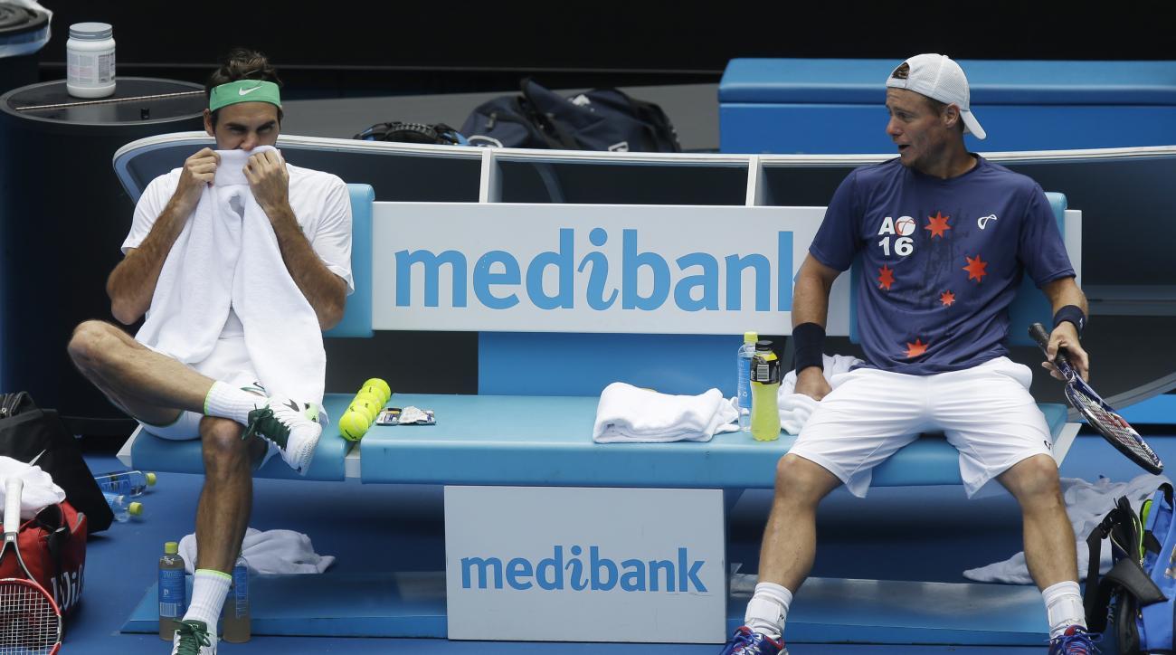 Switzerland's Roger Federer, left, talks with Australia's Lleyton Hewitt during a practice session on Rod Laver Arena ahead of the Australian Open tennis championships in Melbourne, Australia, Friday, Jan. 15, 2016.(AP Photo/Mark Baker)