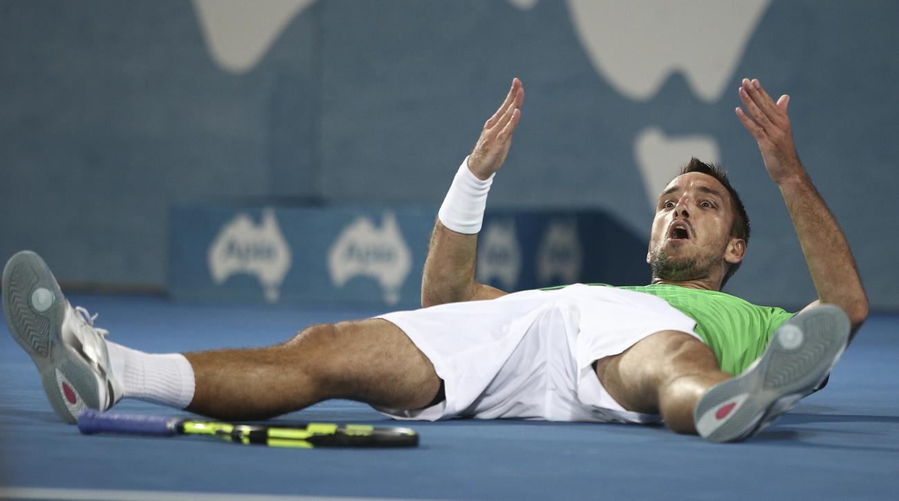 Viktor Troicki of Serbia lies down on the court as he celebrates winning the men's final against Grigor Dimitrov of Bulgaria  at the Sydney International Tennis tournament in Sydney, Australia, Saturday, Jan. 16, 2016.(AP Photo/Rob Griffith)