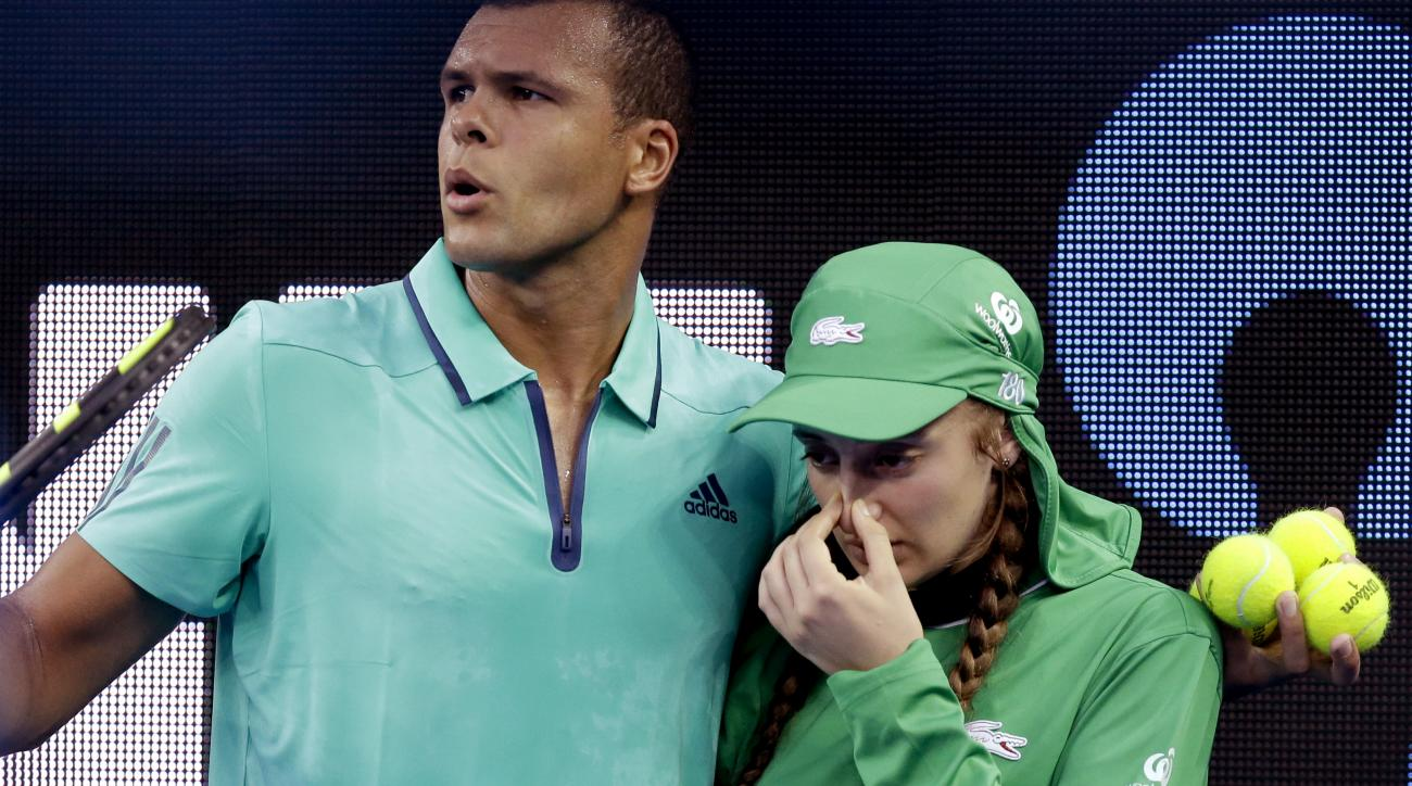Jo-Wilfried Tsonga of France assists a ball girl from the court who was unwell during his second round match against Omar Jasika of Australia at the Australian Open tennis championships in Melbourne, Australia, Wednesday, Jan. 20, 2016.(AP Photo/Aaron Fav
