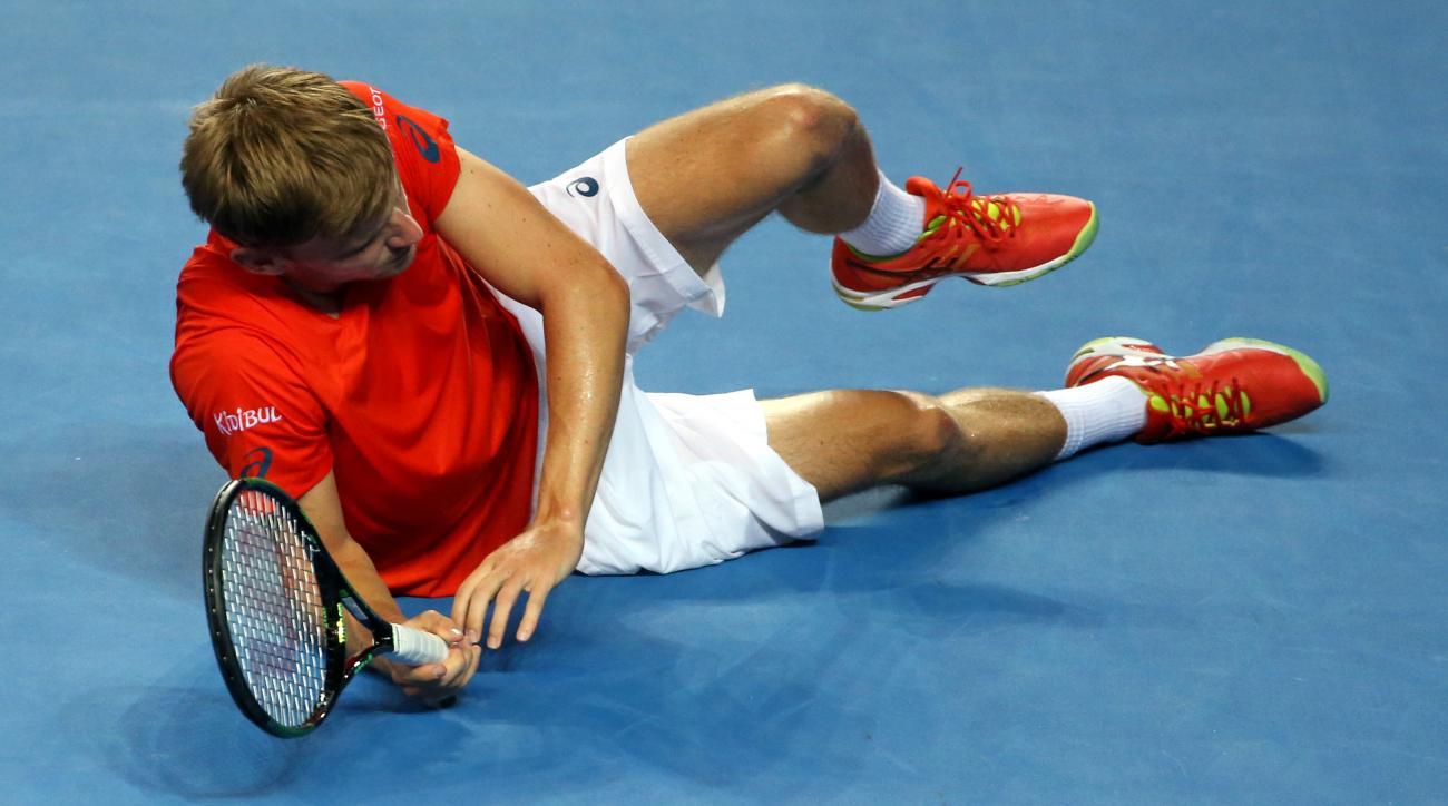 David Goffin of Belgium falls to the court during his third round match against Dominic Thiemof Austria at the Australian Open tennis championships in Melbourne, Australia, Friday, Jan. 22, 2016.(AP Photo/Rick Rycroft)