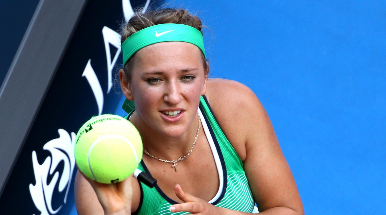 Victoria Azarenka of Belarus prepares to throw an autographed ball back into the crowd after defeating Barbora Strycova of the Czech Republic in their fourth round match at the Australian Open tennis championships in Melbourne, Australia, Monday, Jan. 25,