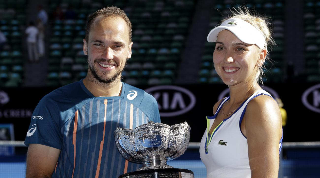 Elena Vesnina, right, of Russia and Bruno Soares of Brazil hold their trophy after defeating Coco Vandeweghe of the United States and Horia Tecau of Romania in the mixed doubles final at the Australian Open tennis championships in Melbourne, Australia, Su